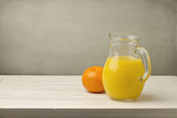 Orange juice with fresh tangerine on white wooden table