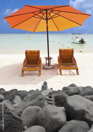 plage mauricienne derrière jetée en rochers noirs