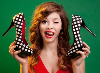 Cheerful girl holding high heels shoes