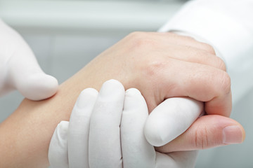 Doctor hand touches and holds the hand of the patient
