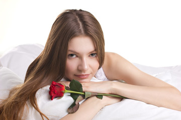 beautiful  woman with rose in a bed