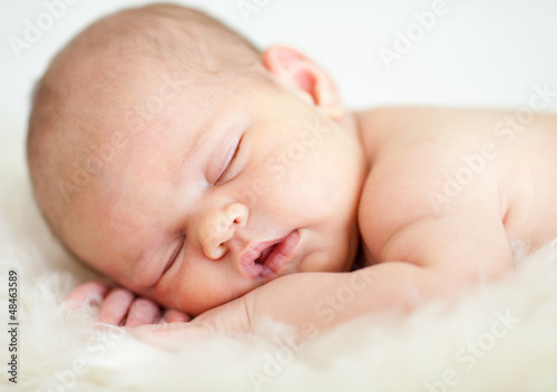 newborn baby girl sleeping on her stomach