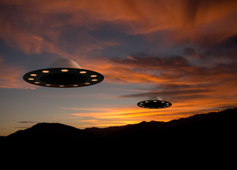 UFO flying saucers over sunset landscape