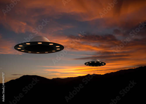 UFO flying saucers over sunset landscape Poster