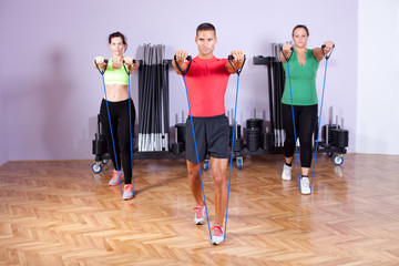 Small group of people doing shoulder exercses using resistance b