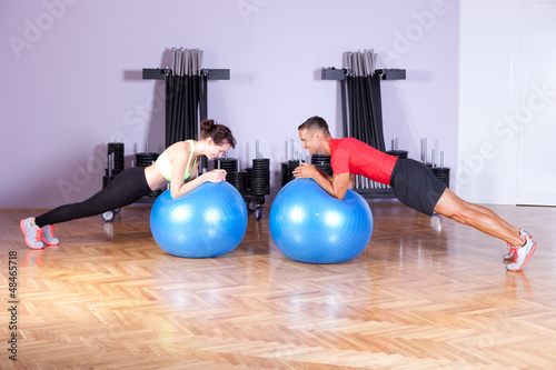 Core / balance training. Couple doing plank exercise using exerc