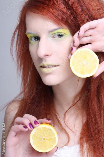portrait of young redhaired girl with lemon