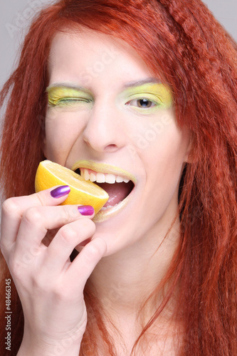 redhaired woman biting the lemon