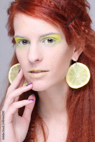 beautiful girl with lemon slices in ears