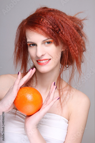 young redhaired woman with orange in her hands