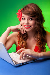 Colorful portrait of smiling young woman working on a laptop
