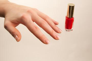 Hand mit rotem Nagellackfläschchen
