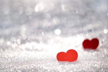 Red hearts in glittering snow with shallow depth of field