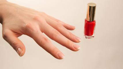 Weibliche Hand mit rotem Nagellackfläschchen