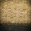 Grunge brick wall and dark stone floor with vignette