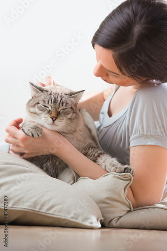 An attractive woman and her cat relaxing on pillows on floor at