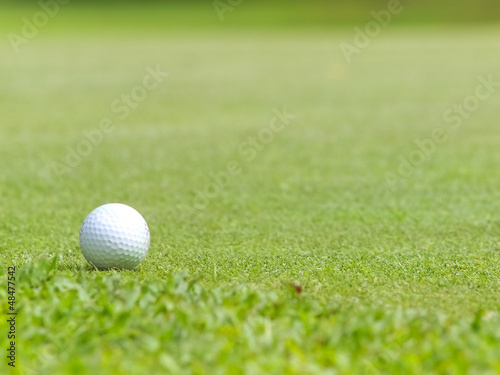Old golf ball on green tee