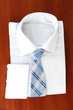 New white man's shirt with color tie on wooden background