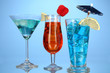 Alcoholic cocktails with ice on blue background