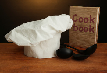 Chef's hat with spoons and cookbook on table on brown
