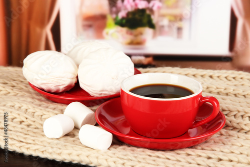 cup of coffee with scarf on table in room