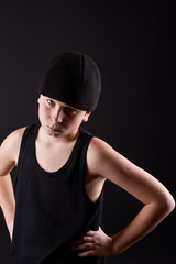 boy in a black T-shirt and a black hat on a black background