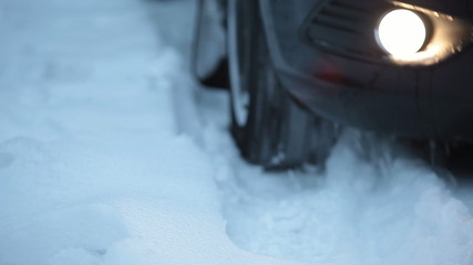 Winter tyres close up on a car in snow going back