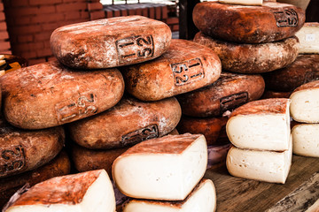Different sorts of Spanish cheese wheels at a market