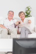 Old couple watching TV and pointing