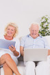 Old couple using a laptop and the tablet