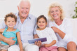 Smiling grandparents with children using a tablet pc