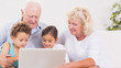 Grandparents with children using a laptop
