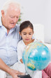 Smiling granddaughter and grandfather with globe