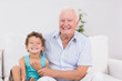Cheerful grandfather and grandson sitting on the sofa