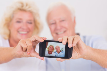 Old couple taking pictures with a smartphone