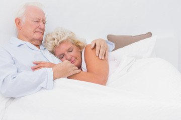 Asleep couple lying on the bed