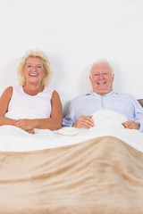 Aged couple lying on the bed
