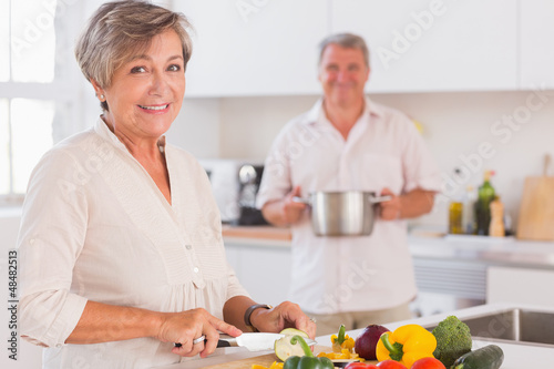 Old couple smiling preparing food