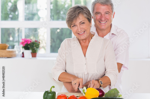 Smiling woman cutting vegetables with her 