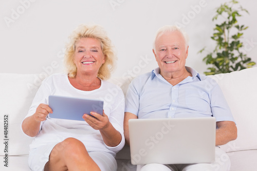 Smiling old couple using a laptop and the tablet