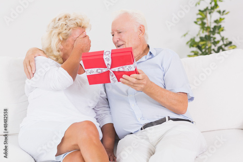 Old man offering a gift to the elderly woman