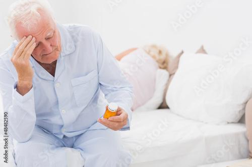 Old man looking at pills
