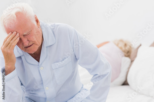 Old man suffering while woman sleeping