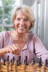 Happy woman playing chess