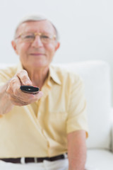 Cheerful elderly man using the remote