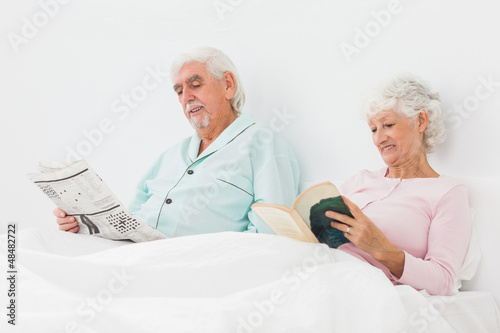 Smiling couple reading in bed