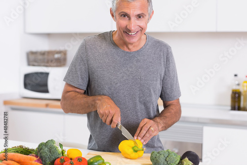 Man cutting a yellow pepper