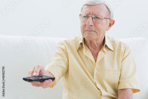 Elderly man using the remote