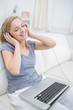 Happy woman listening music through headphones with laptop