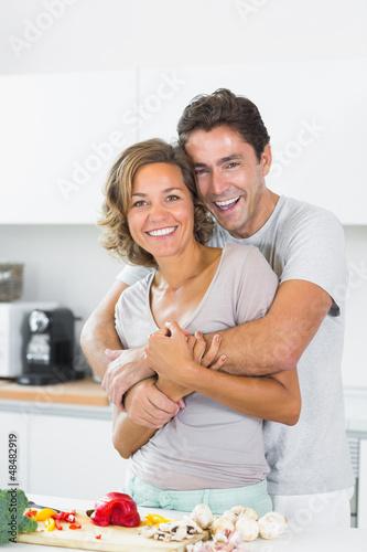 Husband hugging wife at the chopping board